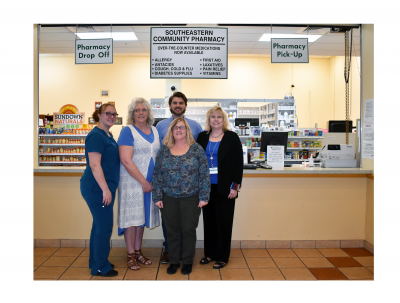The Southeastern Community Pharmacy team in Gainesville posing for a photo in front of the pharmacy for National Pharmacist Day with medication behind them