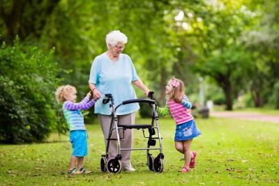 Old woman walking outside with grandchildren